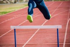 跳在障碍上的运动员 免版税库存照片