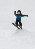 跳在雪滑雪的小男孩 免版税库存照片