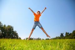 跳在晴朗的草甸的孩子户外 免版税库存图片