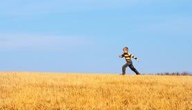 跳少许草甸的男孩喜悦 免版税库存照片