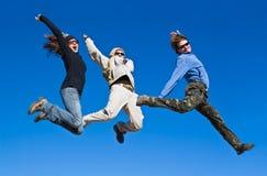 跳山山顶的快乐远足者 免版税库存图片
