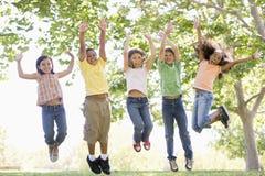 跳户外微笑的年轻人的五个朋友 免版税库存照片