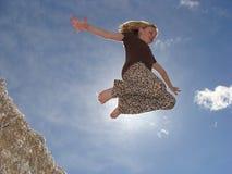 跳棉花种子堆的女孩 免版税图库摄影