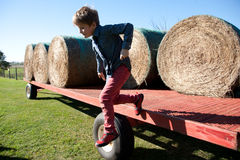跳牵引车拖车的男孩 免版税库存照片