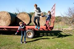 跳牵引车拖车的男孩 免版税图库摄影