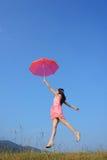 跳红色天空到伞妇女 库存照片