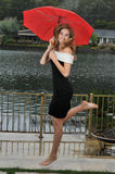 跳红色少年伞的逗人喜爱的女孩下 免版税库存照片