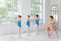 跳舞与个人芭蕾老师的三位小芭蕾舞女演员在舞蹈演播室 免版税库存图片