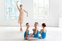跳舞与个人芭蕾老师的三位小芭蕾舞女演员在舞蹈演播室 免版税图库摄影
