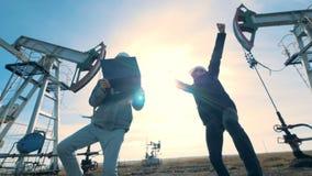 跳舞两位愉快的工程师,获得在油田的乐趣 影视素材