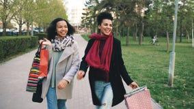 跳舞两名可爱的混合的族种的妇女和获得乐趣,当步行沿着向下有购物袋的时公园 朋友愉快的年轻人 免版税库存照片