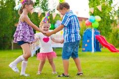 跳舞反复的小调的三个小孩 图库摄影