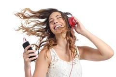 跳舞和听到音乐的愉快的女孩 免版税库存照片