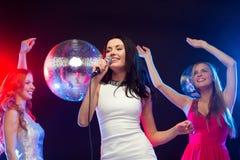 跳舞和唱卡拉OK演唱的三名微笑的妇女 免版税库存照片