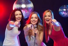 跳舞和唱卡拉OK演唱的三名微笑的妇女 免版税图库摄影
