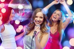 跳舞和唱卡拉OK演唱的三名微笑的妇女 库存照片