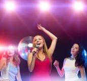跳舞和唱卡拉OK演唱的三名微笑的妇女 图库摄影