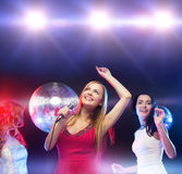 跳舞和唱卡拉OK演唱的三名微笑的妇女 免版税库存图片