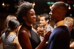 跳舞和喝在晚会的夫妇 免版税库存照片