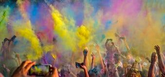 跳舞和庆祝在音乐和颜色节日期间的愉快的青年人 免版税库存照片