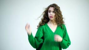 跳舞和挥动她的在手指的一件绿色毛线衣的一个卷曲女孩头发在白色背景 巴黎人女孩在冬天 股票视频