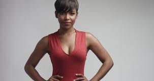跳舞和摆在照相机的红色礼服的混合的族种黑人妇女 免版税库存照片