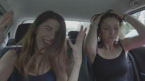 跳舞和欢呼在汽车里面的快乐的十几岁的女孩在假期旅行期间- 影视素材