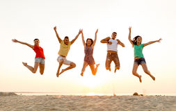跳舞和跳跃在海滩的微笑的朋友 库存照片
