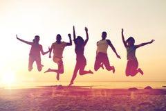 跳舞和跳跃在海滩的微笑的朋友 免版税库存照片