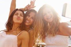 跳舞和采取Selfie的三个十几岁的女孩 免版税库存照片