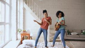 跳舞唱和弹的混合的族种年轻滑稽的女孩在床上的声学吉他 姐妹有乐趣休闲在卧室 库存照片