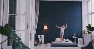 跳舞唱歌与梳子的无线耳机的滑稽的逗人喜爱的女孩和获得乐趣在跳跃在床上的假日早晨 股票视频