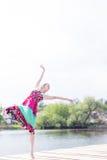 跳舞喜悦:享受舒展在长的轻的礼服的美丽的白肤金发的年轻亭亭玉立的妇女在夏天绿色的水湖户外 图库摄影