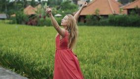 跳舞在一个年轻美丽的女孩的慢动作射击外面在一件红色礼服的米大阳台的有一个豪华的吉普赛人的 影视素材