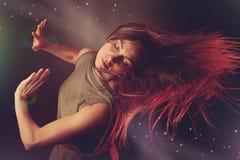 跳舞在与光r的黑暗的背景的美丽的妇女舞蹈家 免版税库存图片
