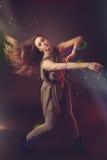 跳舞在与光r的黑暗的背景的美丽的妇女舞蹈家 免版税库存照片