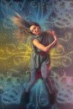 跳舞在与光r的黑暗的背景的美丽的妇女舞蹈家 免版税图库摄影