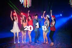 跳舞在与圣诞老人帽子圣诞节节日晚会的夜总会的人 免版税库存照片