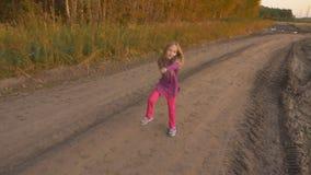跳舞在乡下公路的年轻白种人女孩节律唱诵的音乐 唱歌白白肤金发的长的头发的女孩户外 影视素材