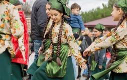 跳舞在人人群的未认出的女孩传统服装的在党期间 库存照片