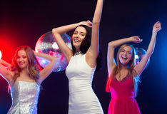 跳舞在俱乐部的三名微笑的妇女 免版税库存照片