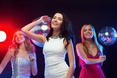 跳舞在俱乐部的三名微笑的妇女 库存图片