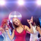 跳舞在俱乐部的三名微笑的妇女 图库摄影