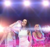 跳舞在俱乐部的三名微笑的妇女 库存照片
