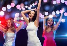 跳舞在俱乐部的三名微笑的妇女 免版税图库摄影