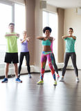 跳舞在健身房或演播室的小组微笑的人民 免版税库存图片