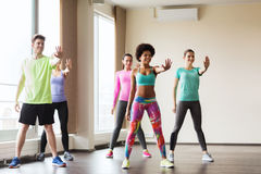 跳舞在健身房或演播室的小组微笑的人民 免版税图库摄影
