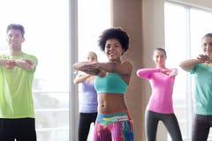 跳舞在健身房或演播室的小组微笑的人民 免版税库存照片