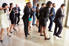 跳舞在办公室大厅的商人和女实业家 库存图片