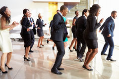 跳舞在办公室大厅的商人和女实业家 库存照片
